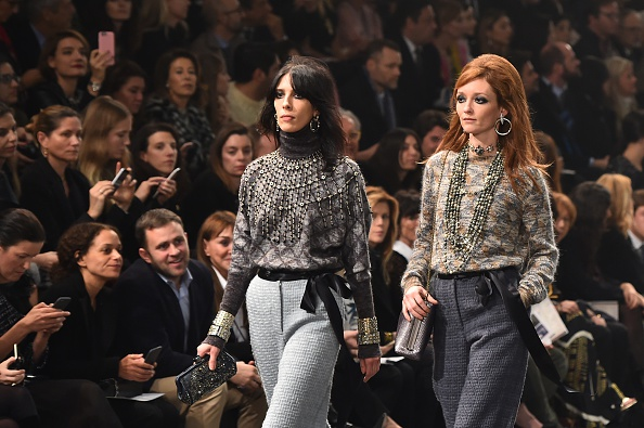 "US model Jamie Bochert and french model Audrey Marnay present creations during the 12th Chanel Metiers dArt show ""Paris-Rome"", an annual event to honor craftsmanship that artisan partners bring to the houses collections, on December 1, 2015 at the Cinecitta studios in Rome.  AFP PHOTO / GABRIEL BOUYS / AFP / GABRIEL BOUYS        (Photo credit should read GABRIEL BOUYS/AFP/Getty Images)"